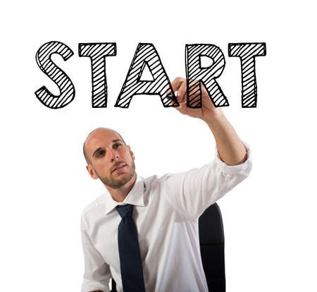 Businessman writing the word start with a pen