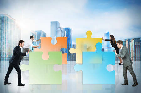 Concept of teamwork and partnership. Businesspeople pushing pieces of puzzle fit together. Stock Photo