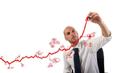 Businessman draw graphics on an arrow uphill 写真素材