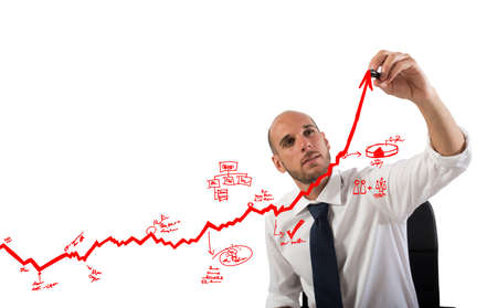 Businessman draw graphics on an arrow uphill Foto de archivo