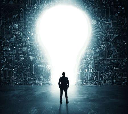 Hombre de negocios mira un gran agujero en la forma de una bombilla de luz en la pared Foto de archivo - 64803573