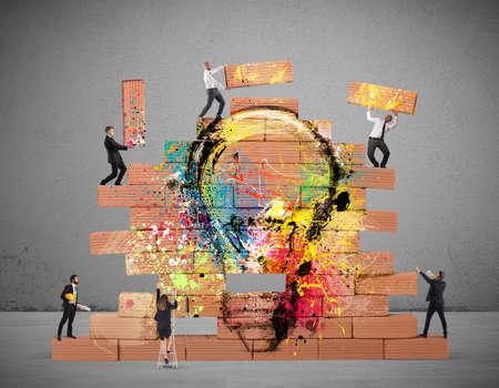 Bedrijfs persoon bouwde samen een grote bakstenen muur met getekende gloeilamp