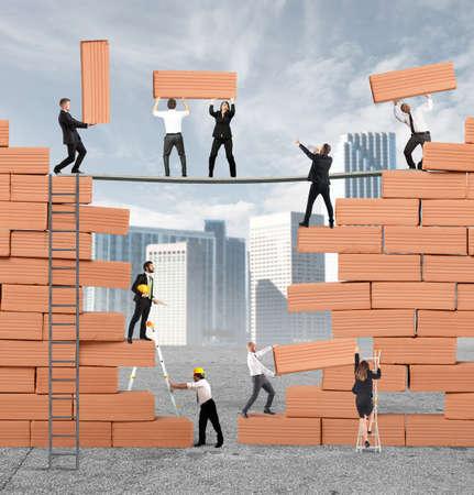 Bedrijfs persoon bouwde samen een grote bakstenen muur Stockfoto