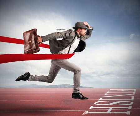 El hombre de negocios con la bolsa va más allá de la cinta roja a la llegada de una carrera Foto de archivo - 64803574