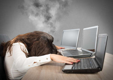 hard: Stressed businesswoman due to overwork against laptop