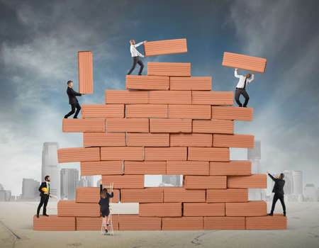 Business person built together a big brick wall Stock Photo
