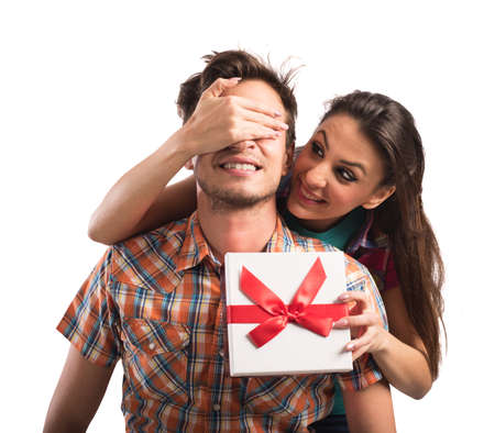 gives: Girl covers eyes boy while gives to him a gift box Stock Photo