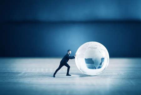 Zakenman duwen een wereld glazen bol met continenten op de tafel Stockfoto