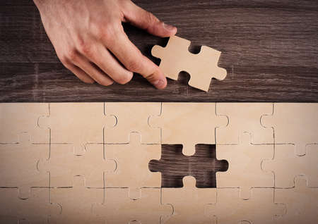 complete solution: Businessman complete a puzzle inserting last piece Stock Photo