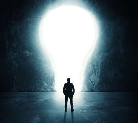 Businessman looks at a big hole in the shape of a light bulb on the wall