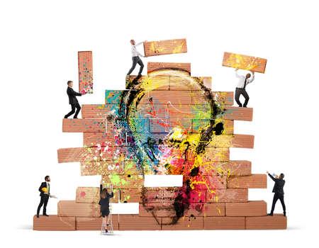 비즈니스 사람이 함께 그려진 된 전구 큰 벽돌 벽을 구축 스톡 콘텐츠