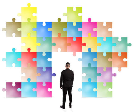 Man looks a puzzle built with colored pieces Stock Photo