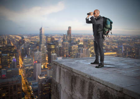find: Businessman with backpack and binoculars watching from above the city Stock Photo