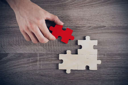 missing piece: Businessman complete a puzzle inserting a missing piece