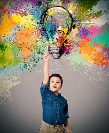 Child indica una bombilla de color grande diseñado Foto de archivo