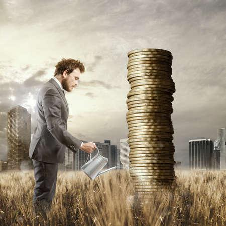 Geschäftsmann Bewässerung Geldmünzen, als ob sie Pflanzen waren Standard-Bild - 63516782