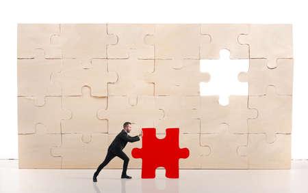 El hombre de negocios completar un rompecabezas inserción de una pieza de color rojo que falta