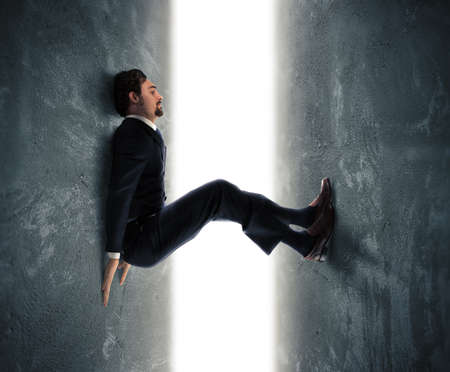 trapped: Businessman man trapped between two walls strives to push