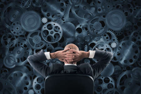 business gears: Businessman sitting in a chair watching and analyzing a wall of the gear mechanisms