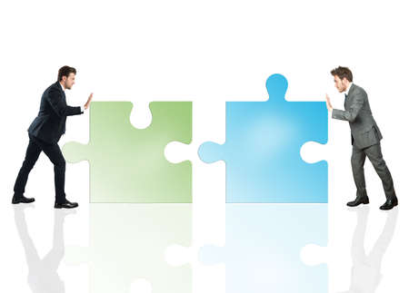 Businessmen push a pieces of puzzle fit together