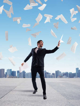 rejoices: Businessman in a roof of skyscraper rejoices throwing sheets