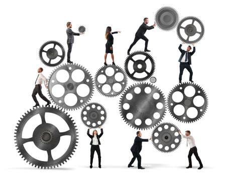 Teamwork of businesspeople work together to a system of gears Banco de Imagens