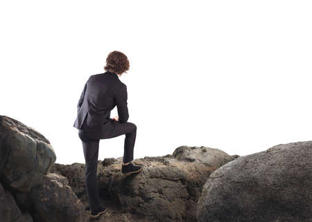 Businessman leaning on a rock watching the horizon Imagens