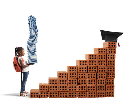 Child with backpack and study books climbs a bricks scale Stock Photo