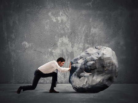 Businessman pushing a heavy boulder with great effort