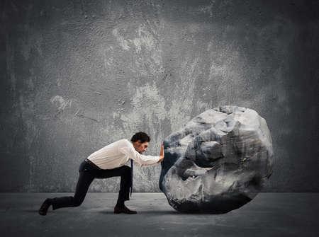 Zakenman duwen van een zware rotsblok met veel moeite Stockfoto