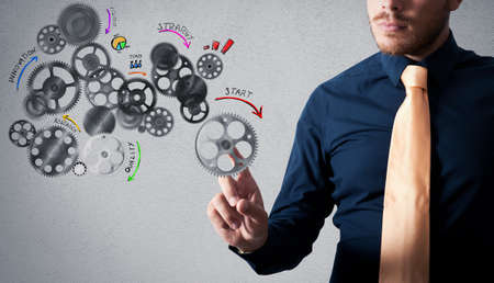 Businessman touching an analysis project with gear mechanisms designed Stock Photo
