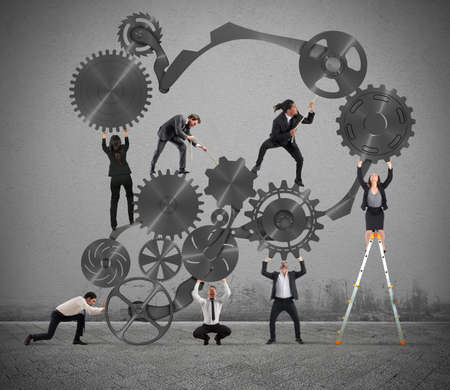 gearwheel: Teamwork of businesspeople work together to a system of gears Stock Photo