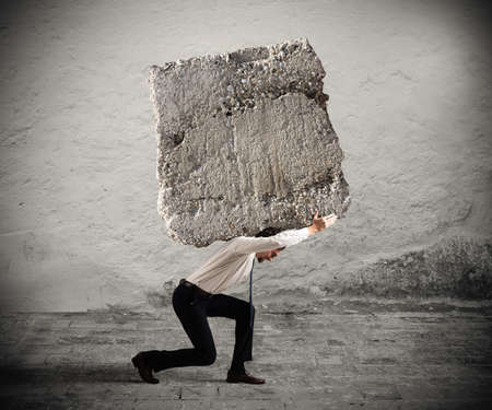 heavy: Businessman walking with a heavy boulder on his back