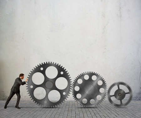pushes: Businessman pushes a system mechanism of gears