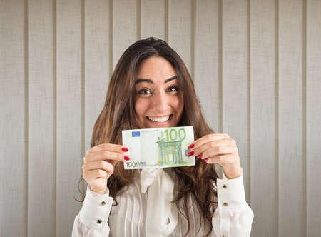 exult: Happy businesswoman shows a 100 euro banknote