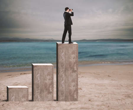 enterprising: Businessman looks at the economic future with binoculars over a statistic Stock Photo