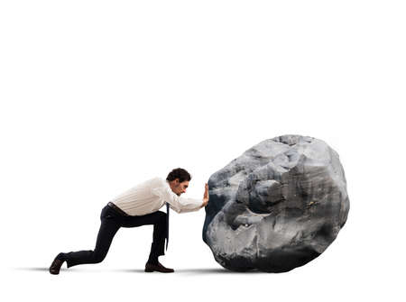 impediment: Businessman pushing a heavy boulder with great effort