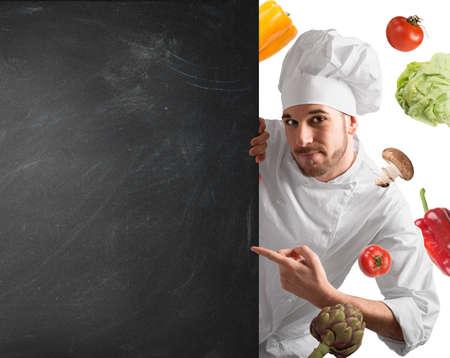 comidas saludables: Cocinero sonriente con pizarra y hortalizas fondo