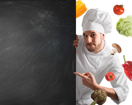 healthy foods: Smiling chef with blackboard and vegetables background