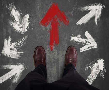 flechas direccion: El hombre de negocios decidió dirección y sigue la flecha roja Foto de archivo