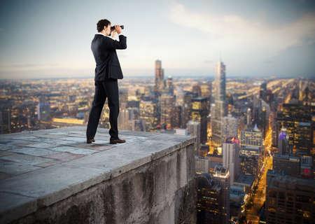ビジネスマンが双眼鏡で屋根から都市を見てください。