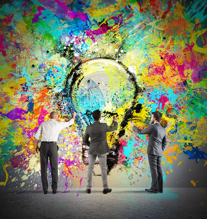 Business person paint together a big colored lightbulb on the wall