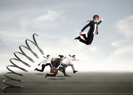 business rival: Businessman jumping on a spring during a race with opponents Stock Photo