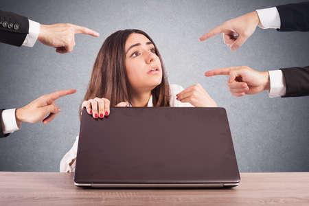 Las personas que apuntan a una mujer oculta detrás de una computadora