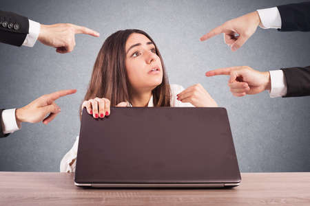 displeasure: People pointing a woman hidden behind a computer Stock Photo