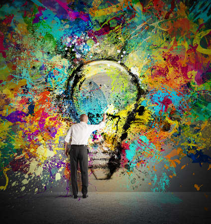 paints: Businessman draws on the wall a big colored bulb with bright colors