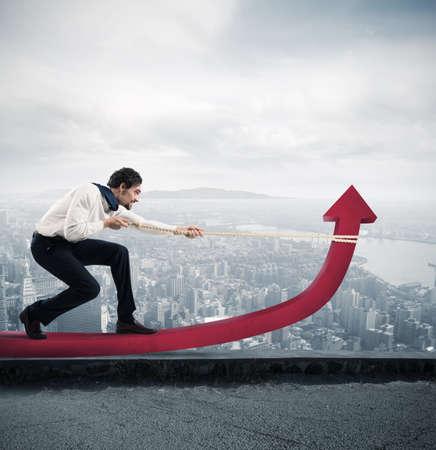 ganancias: empresario determinado con mucho esfuerzo levanta estadísticas flecha con una cuerda en una azotea del rascacielos