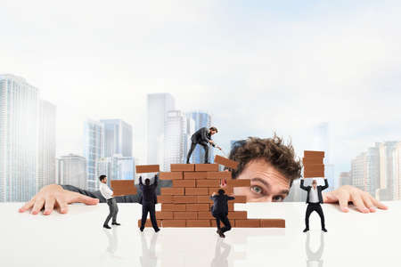work together: Businessman watches a teamwork of businesspeople work together by building a brick wall Stock Photo