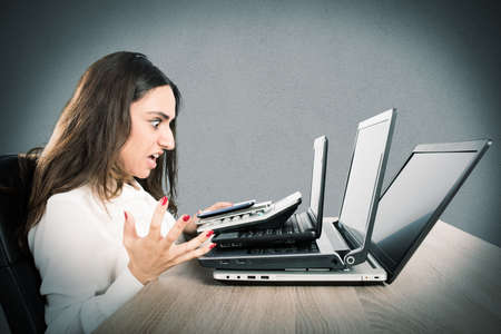 Businesswoman with an angry expression and stressed front of three laptops Stock Photo
