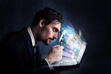 infect: Businessman look with magnifying glass at the computer screen